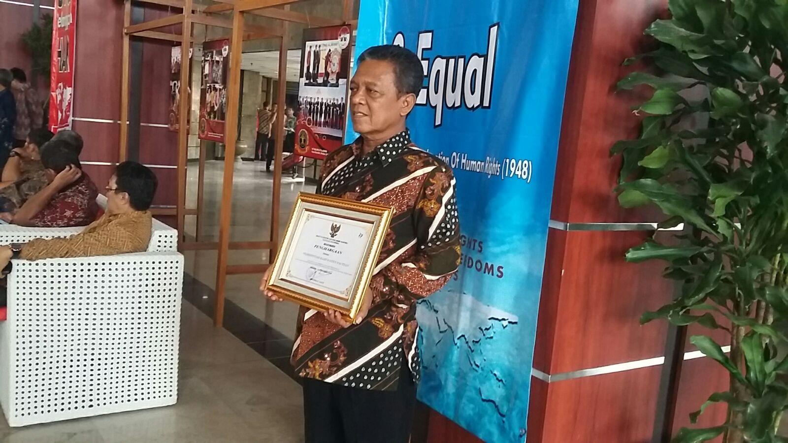 BUpati Indartato menerima piagam penghargaan kabupaten peduli HAM. (Foto: Wasi Prayitno/Pacitanku CJ)